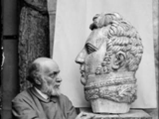 """Antoine Bourdelle (1861-1929),  assis près de la tête monumentale du Général """"Alvear"""". Photographie anonyme. Paris, musée Bourdelle."""